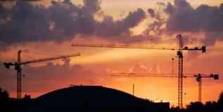 Puesta del sol con las grúas Foto de archivo