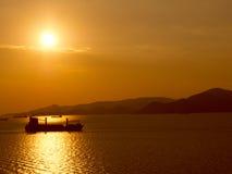 Puesta del sol con las naves en el ancla Imagenes de archivo