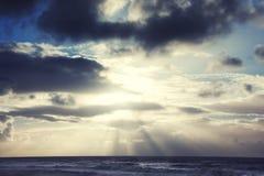 Puesta del sol con las nubes oscuras y el cielo azul sobre el mar Imagen de archivo libre de regalías