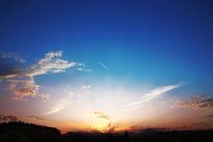 Puesta del sol con las nubes, rayos ligeros, cielo azul, fondo natural En Fotos de archivo