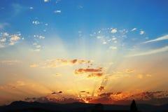 Puesta del sol con las nubes, rayos ligeros, cielo azul, fondo natural En Fotografía de archivo