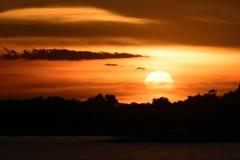 Puesta del sol con las siluetas de árboles y del agua imagenes de archivo
