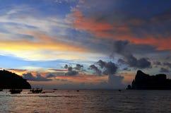 Puesta del sol con los barcos de la cola larga en la bahía de Loh Dalum en la isla de Phi Phi Foto de archivo