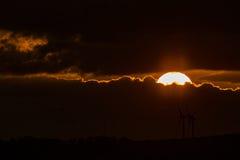 Puesta del sol con los molinoes de viento Foto de archivo libre de regalías