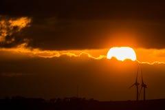 Puesta del sol con los molinoes de viento Imagen de archivo
