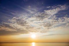 Puesta del sol con los rayos y las nubes del sol Imagenes de archivo