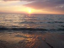 Puesta del sol contra la orilla Fotografía de archivo libre de regalías
