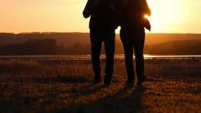 Puesta del sol de dos amigos a ir adelante, el concepto de viaje de la aventura, una mochila en los hombros