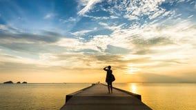 Puesta del sol de fotografía de la mujer en el embarcadero en el mar Imagen de archivo