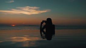 Puesta del sol de fotografía de la muchacha en el océano que se sienta en la piscina almacen de video