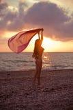 Puesta del sol de goce modelo de la muchacha delgada en la playa con el cielo hermoso imágenes de archivo libres de regalías