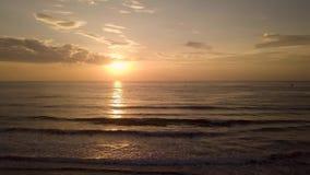 Puesta del sol de igualación hermosa en cielo sobre el mar en la playa arenosa Gente del grupo en la motocicleta que mira salida  almacen de video