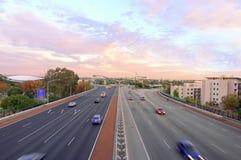 puesta del sol de la autopista sin peaje tirada con tráfico Imagenes de archivo