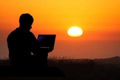 Puesta del sol de la computadora portátil del hombre Imagen de archivo libre de regalías