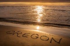 Puesta del sol de la costa de Oregon, texto escrito en la playa imagenes de archivo