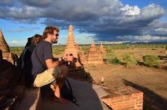 Puesta del sol de la foto del tiroteo de la espera del viajero con la ciudad antigua Bagan, Myanmar Foto de archivo libre de regalías