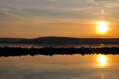 Puesta del sol de la orilla del agua. Fotografía de archivo