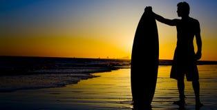 Puesta del sol de la persona que practica surf foto de archivo libre de regalías
