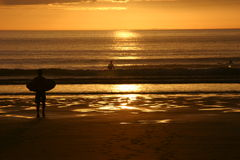 Puesta del sol de la persona que practica surf @ Foto de archivo libre de regalías