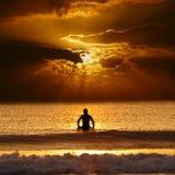 Puesta del sol de la persona que practica surf que espera Imagen de archivo libre de regalías