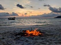 Puesta del sol de la playa con la hoguera y el barco fotos de archivo