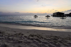 Puesta del sol de la playa con la opinión oscura de la casa de planta baja Imágenes de archivo libres de regalías