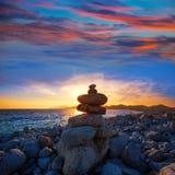 Puesta del sol de la playa del DES Falco del casquillo de Ibiza con las piedras del deseo Fotos de archivo