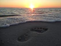 Puesta del sol de la playa de la Florida con huellas en arena imagen de archivo