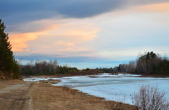 Puesta del sol de la primavera en el río que fluye debajo de los acantilados Hielo azul en el río Fotografía de archivo