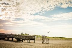 Puesta del sol de la silla del salvavidas del embarcadero de la playa Imágenes de archivo libres de regalías