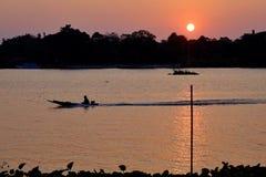 Puesta del sol de la silueta con un femenino remando un bote pequeño en el río imagenes de archivo