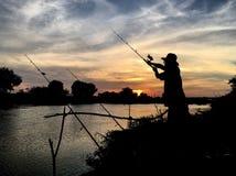 Puesta del sol de la silueta del pescador Fotos de archivo libres de regalías