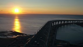 Puesta del sol de la tarde de la visión aérea en el mar y el coche que mueven encendido el puente de la carretera en ciudad almacen de metraje de vídeo