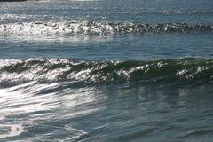 Puesta del sol de las ondas de la rotura del punto que practica surf imagen de archivo libre de regalías
