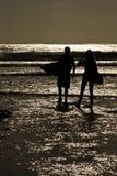 Puesta del sol de las personas que practica surf Foto de archivo