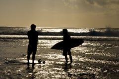Puesta del sol de las personas que practica surf Imagenes de archivo