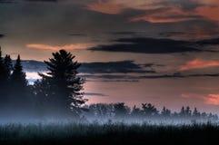 Puesta del sol de niebla en el país Imagenes de archivo