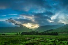 Puesta del sol de niebla sobre las montañas de Glencoe en Escocia fotos de archivo