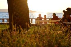Puesta del sol de observación de la familia en la playa Imágenes de archivo libres de regalías