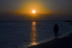 Puesta del sol de observación de la mujer sola Imágenes de archivo libres de regalías