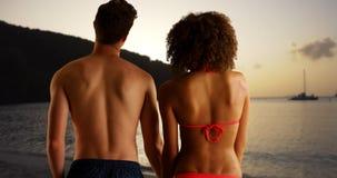 Puesta del sol de observación de los pares felices de la raza mixta de la playa Foto de archivo