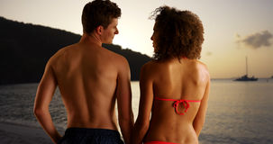 Puesta del sol de observación de los pares felices de la raza mixta de la playa Imágenes de archivo libres de regalías
