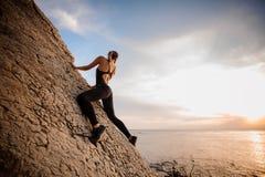 Puesta del sol de observación femenina del escalador de roca sobre el mar fotos de archivo
