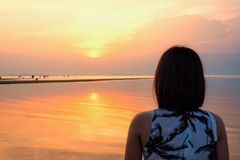Puesta del sol de observación de la mujer en la playa Fotos de archivo