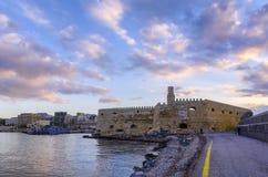 Puesta del sol de Olorful sobre el puerto veneciano viejo de ciudad y de la fortaleza Koules de Heraklion fotos de archivo