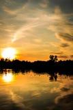 Puesta del sol de oro de la hora en el río con la reflexión en el agua Foto de archivo