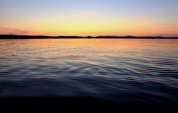 Puesta del sol de oro en el lago Foto de archivo