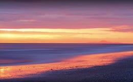 Puesta del sol de oro en la playa Foto de archivo libre de regalías