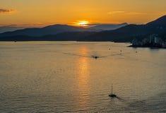 Puesta del sol de oro hermosa sobre el océano y las montañas Imagen de archivo libre de regalías