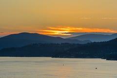 Puesta del sol de oro hermosa sobre el océano y las montañas Foto de archivo libre de regalías